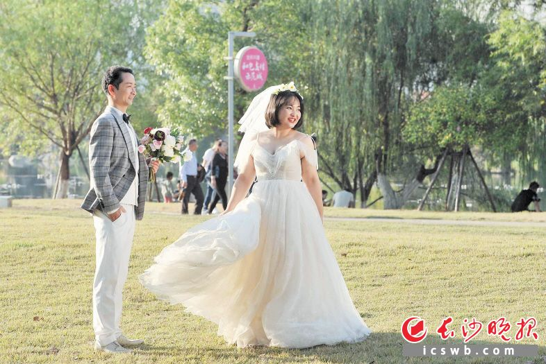 →梅溪湖节庆岛上,一对新人在美景中拍摄婚纱照。