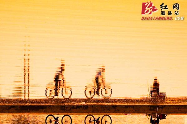 9月5日,在道县西洲公园拦水坝上,瑜伽爱好者和骑行爱好者在凉凉清风中进行晨练,缓缓的秋水、清秋的晨霞、忙碌的渔夫以及独钓者,相互映衬,动静结合,勾勒出一幅和谐幽静而又富有生机的清秋图。