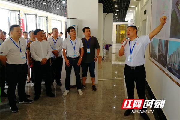 黄建龙(右一)向皮具产业研讨会参会人员介绍项目规划。。.jpg