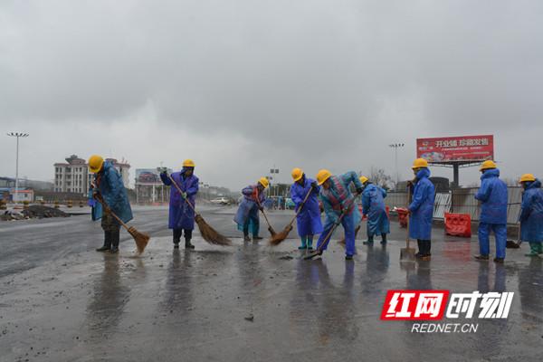 施工人员正冒雨清理碎石、泥土等杂物,以便晴好天气时进行面层沥青摊铺作业。.jpg