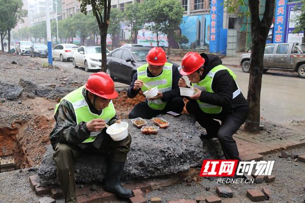 唐海元(中)与队员们在维修现场吃盒饭。.jpg