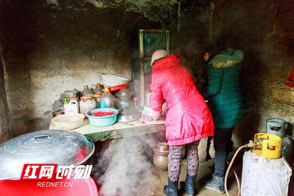 """邻里的家庭主厨正围着灶台做年猪肉,准备""""杀猪饭""""供大家分享。"""