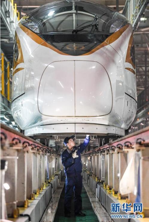 南京南动车所的工作人员在检查维护列车的走行部(1月19日摄)。  春运在即,南京动车段南京南动车所百余名工作人员彻夜奋战,重点加强对高铁列车转向架、受电弓等行车安全关键部件和厕所、饮水设施、座椅等客服设施的检查维护,为旅客提供安全舒适的出行体验。