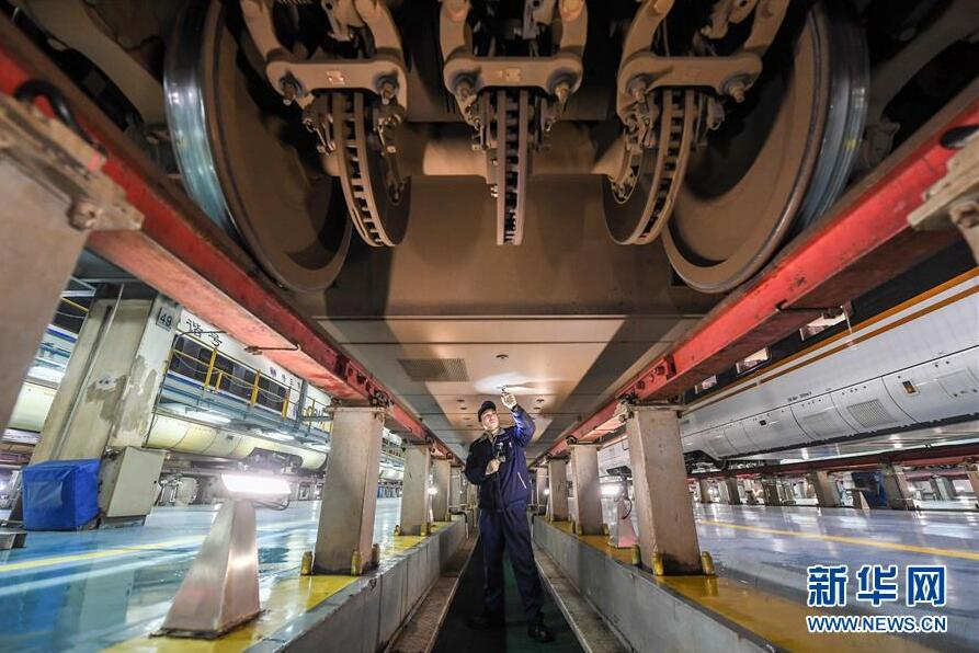 南京南动车所的工作人员在检查维护列车的底板螺栓(1月19日摄)。
