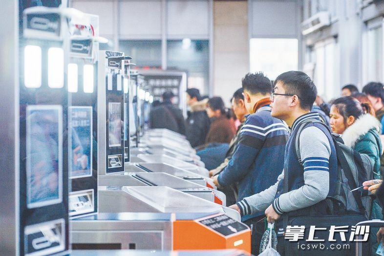 昨日,在长沙火车站进站口,旅客正在通过人脸识别验票系统进入车站。长沙晚报全媒体记者 邹麟 摄
