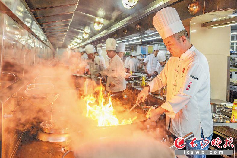 """大年三十,火宫殿团圆宴年夜饭的""""总掌勺""""李强正带领后厨200多名大厨和配菜员给客人准备年夜饭。  长沙晚报全媒体记者 陈飞 摄"""