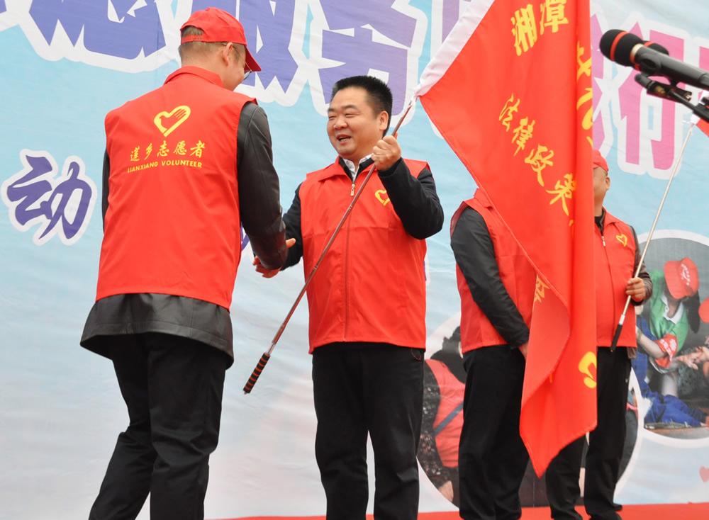 启动仪式上,湘潭县委书记傅国平为9支志愿服务队授旗。
