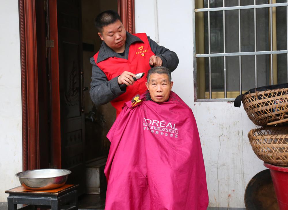 志愿服务队在敬老院为老人理发。
