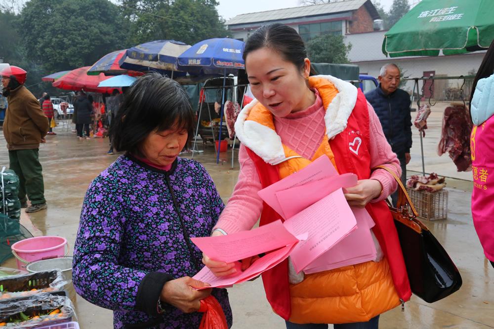 志愿服务者为群众发放宣传资料。