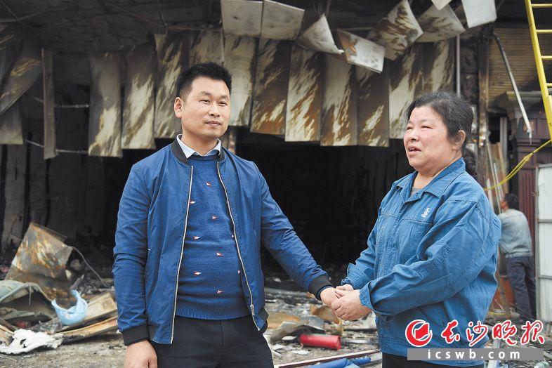 昨日,在起火楼房前,胡定菊拉着救人小伙张文清的手,内心充满感激。  长沙晚报全媒体记者 刘琦 摄