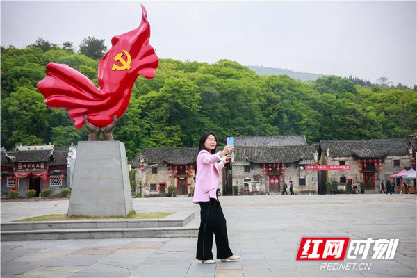 沙洲村民俗广场前,黄玲会讲起沙洲村的红色故事。.jpg