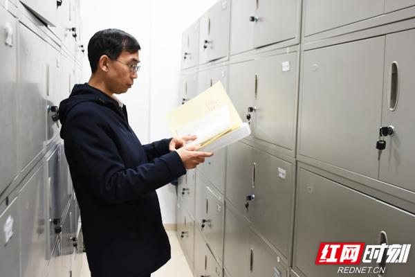 李华在查阅集团干部档案。