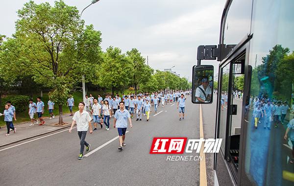 霎时间淹没在一片蓝色的厂服中。员工还可以乘坐免费公交车上下班。李磊摄。.jpg