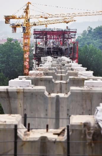 """4月27日,张吉怀高铁麻阳尧里河特大桥桥墩主体已基本完工,中铁十四局工人在进行预制箱梁施工。  """"五一""""前夕,记者走进张吉怀高铁建设工地,用镜头记录了高铁建设者忙碌的身影。  张吉怀高铁(张家界-吉首-怀化)客运专线,是国家重点建设工程,总投资382.4亿元,于2016年 12月开工建设,建设工期5年。线路全长247.48公里,衔接黔张常、沪昆客运专线、怀邵衡等铁路线,辐射武陵山片区,途经3市州8个县(区)37个乡镇,是一条地质构造复杂、地形地貌多变、桥隧比例高的山区高速铁路。"""