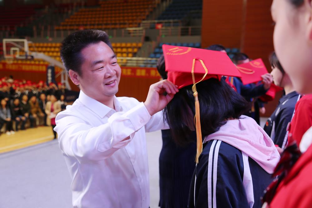 县委书记傅国平等为青年代表佩戴成人帽,并赠送《中华人民共和国宪法》手册