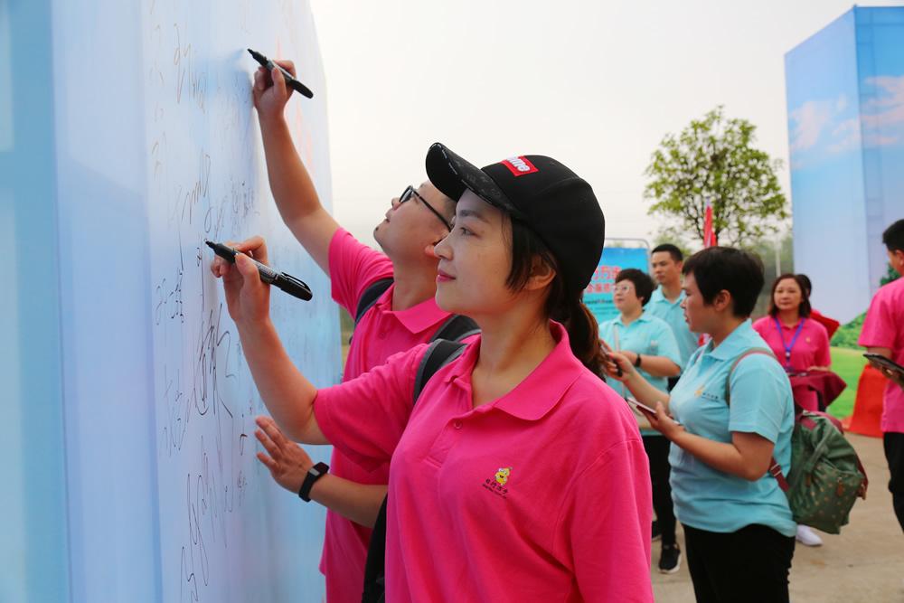 参加活动的队员在活动签名墙上签名。