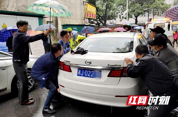 图一  警民携手抬移车辆.jpg