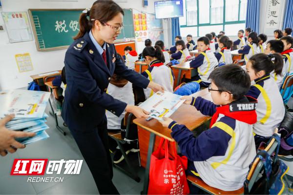 图为 株洲市税务局在北京师范大学株洲附属学校开设税收小课堂,并现场派送减税礼包,嘱咐学生自学的同时把减税礼包带给家人_meitu_2.jpg