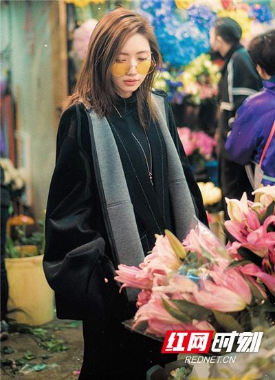 刘惜君为市场鲜花的美丽驻足。