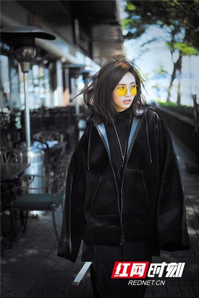 刘惜君身穿黑色卫衣搭配复古墨镜漫步在香港街头。
