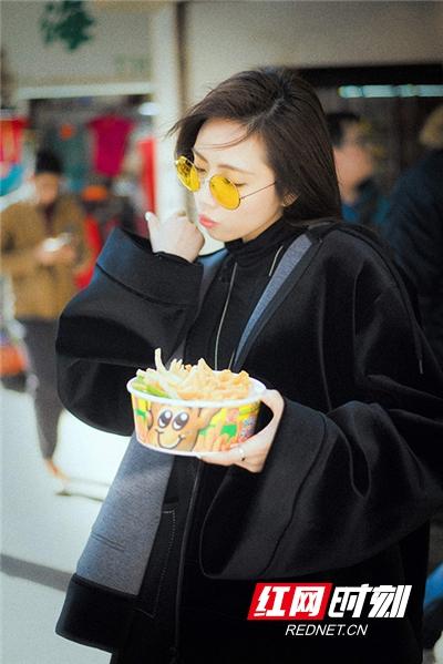 刘惜君在各类港式招牌下吃着薯条。
