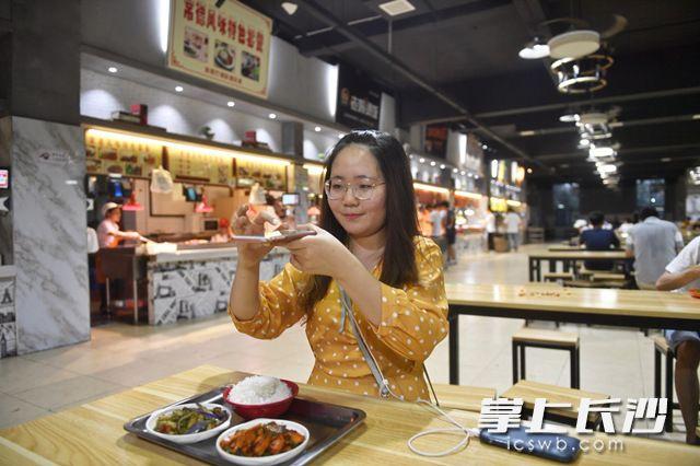 6月3日,湖南涉外经济学院毕业生、新疆姑娘全雪苗用手机拍下自己在学校食堂品尝的美食。长沙晚报全媒体记者 余劭劼 摄