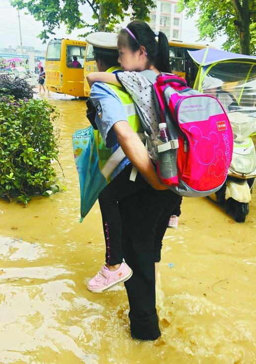 6月10日,新田县龙泉第五完全小学,民警护送三年级(10)班学生到安全地带。当天,该县遭遇强降雨,位于舂陵河畔的龙泉第五完全小学被倒灌的河水浸漫,学校立即启动紧急预案。(刘忠平 摄)