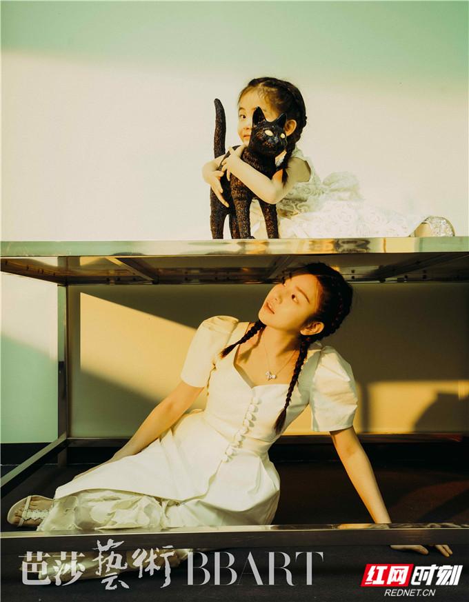 在另一幅画面中,陈妍希身穿复古的白裙,扎着两条辫子,眼神里透露的纯真与抱着黑猫的小女孩别无二致,整体画面超和谐。