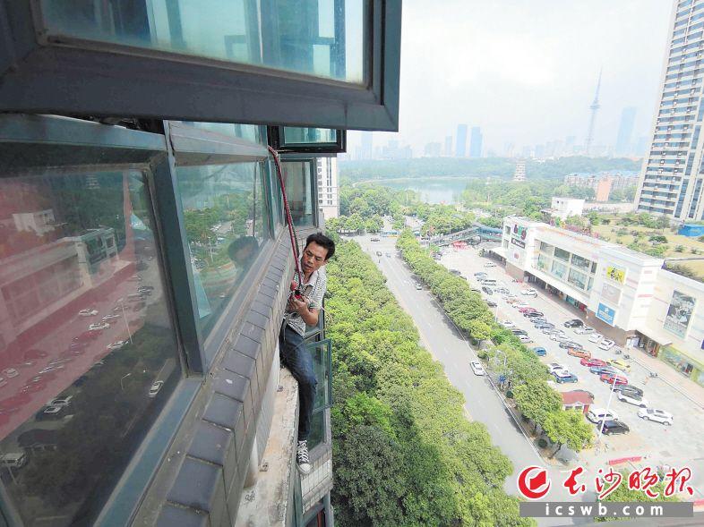 ↑肖建华骑在墙外在为市民修空调。