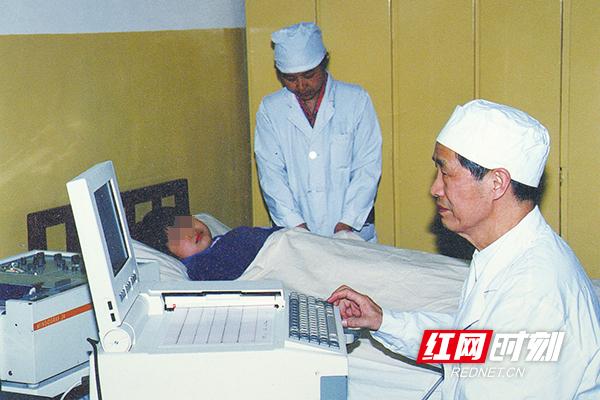 上世纪80 年代,湘雅二医院谢振武教授(右一)为患儿做心功能检查。(图片来源:湖南省卫生健康委宣传处)