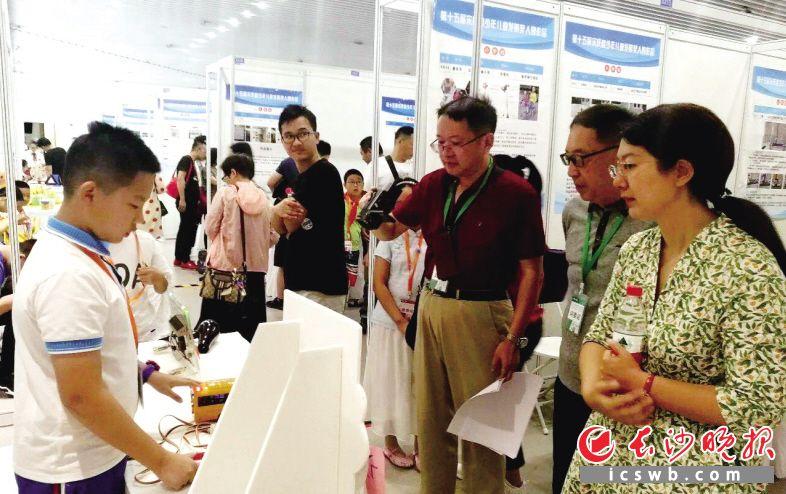 比赛现场,胡皓博向参观者讲解自己的作品。枫树山小学 供图