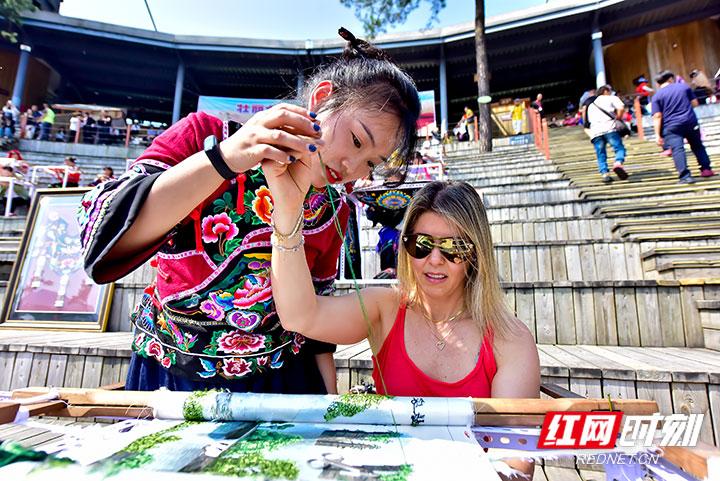 9月28日,2019·首届武陵山区(张家界)刺绣大赛在张家界大峡谷玻璃桥上举行,近70名民间刺绣艺人,带着她们手中的针线和画笔,在现场穿针引线、切磋技艺,用灵巧的双手向游客展现精湛的刺绣技艺。(摄影 张潘)