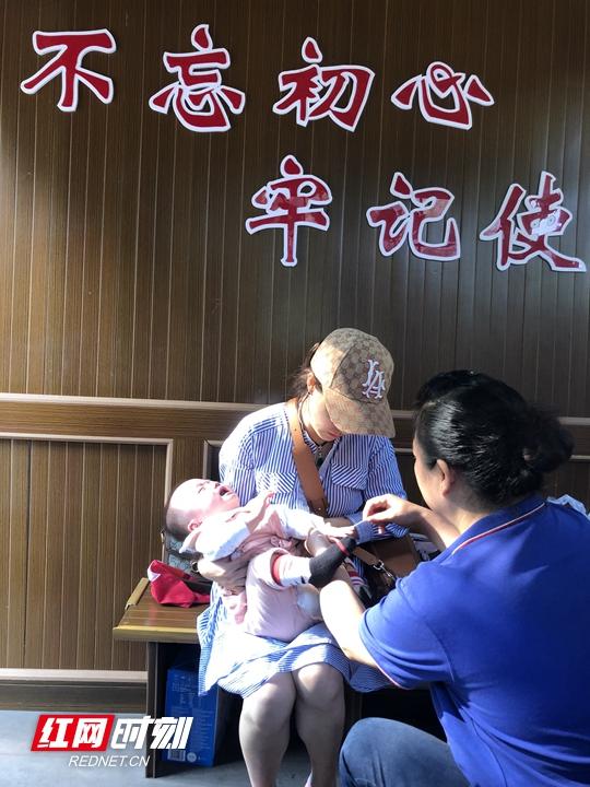 张管局琵琶溪管委会党员杨贵辉给婴儿伤口擦药消毒.jpg