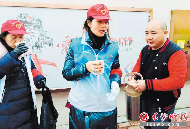 湖南好人吴鑫成(右一)给寒冬街头工作的环卫工、协管员以及志愿者送来热腾腾豆浆和包子。 长沙晚报通讯员 范辉云 摄