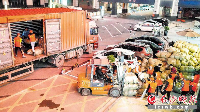 12月4日晚,长沙县新长海数码广场,志愿者合力将400个冬衣包裹装车,发往西藏。长沙晚报通讯员 盛磊 摄