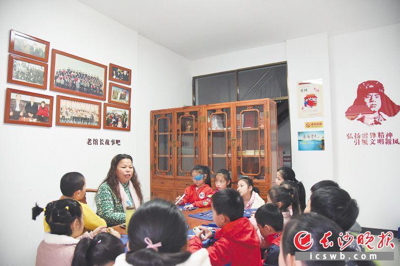 麓谷街道和馨园社区的老馆长故事吧内,雷锋的堂侄女雷伯元给孩子们讲雷锋学习的故事。              长沙晚报全媒体记者 刘琦 摄