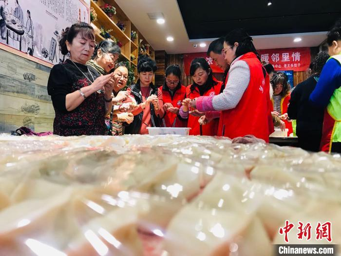"""图为""""银发志愿队""""成员包饺子实况。 艾庆龙 摄"""
