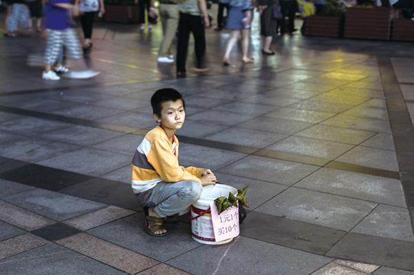 2018年夏天,賀再亮在街頭無意看到了這個賣粽子的小男孩。與街頭的喧鬧形成對比,這個小男孩的臉上有著與同齡人完全不一樣的成熟。端起隨手帶著的相機,賀再亮定格了這一刻。然而,就在他翻看照片時,小男孩的母親小心翼翼地靠過來,請求賀再亮再給她的兒子多拍幾張。 原來,小男孩與母親來自農村,家境一般,母子倆利用假期自制了一些粽子運到瀏陽來賣。讓人感慨的是,小男孩從小到大沒有拍過一張像樣的照片,而這一天恰巧是他10歲的生日。