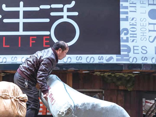 2019年1月21日,在蛟龍巷,一名工人站在車上卸貨。雖然工作比較累,但他的眼中滿是堅定,或許這便是為了美好生活奮斗的姿態。