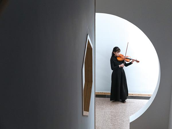 2019年2月19日,在集里橋社區一處走廊上,一名小女孩正專注地拉著小提琴,這里是她一個人的舞臺。