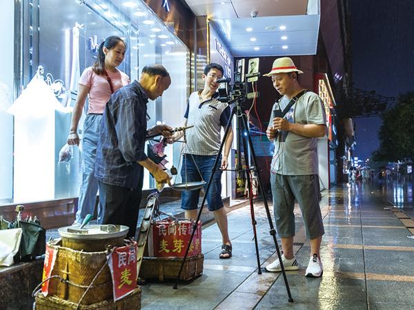 2019年6月22日,新文路步行街上,一名老人挑著一擔麥芽糖在叫賣,一名在街上做視頻直播的市民對此進行了直播。