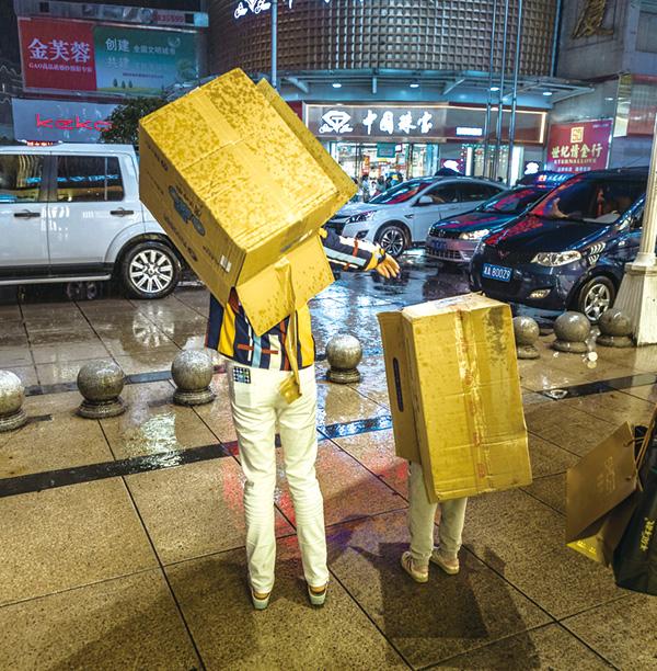 2018年5月11日,一對母女正在新文路步行街邊等待的士。此時正在下雨,為了避雨,母親找來兩個紙箱子,用來給兩人遮雨。