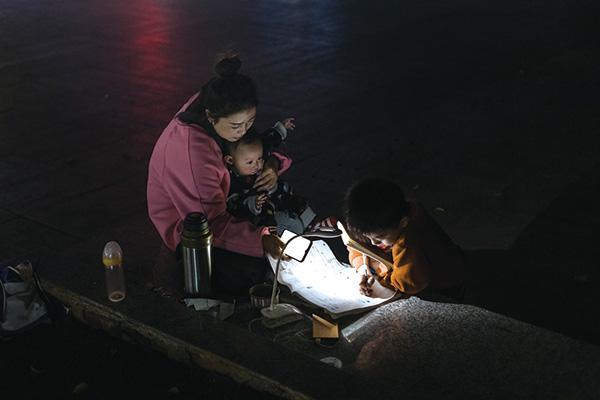 2019年10月30日,譚嗣同故居廣場,打開一盞臺燈,一名小男孩趴在路邊的石階上做作業。察覺到光線不夠亮,坐在一旁的孩子母親趕緊拿出手機來照明。