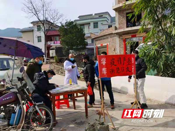 宁远县和平村,工作人员在卡口为过往群众测体温。_副本.jpg