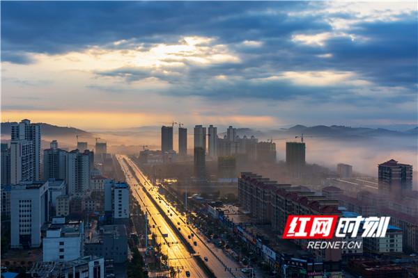 城市楼宇笼罩在升腾的平流雾之中,城市建筑被云雾缠绕,若隐若现,蔚为壮观,宛若一幅徐徐展开的壮美画卷。