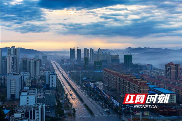 2月14日,湖南省永州市东安县城区,在云雾的烘托下,红日从东边冉冉升起,染红了天空和大地。