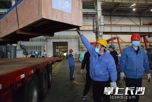 工人们小心翼翼地将主轴吊装安放到加长运输车上。岑军 摄