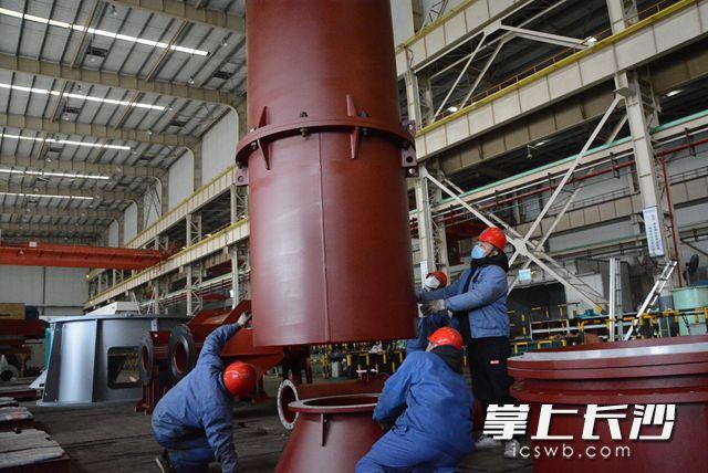 在总装车间里,工人们组装长达8米的斜流泵。岑军 摄