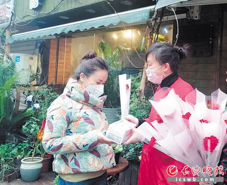 牛角塘社区的党员为辖内门店女老板送上口罩和鲜花。 长沙晚报全媒体记者 胡媛媛 摄