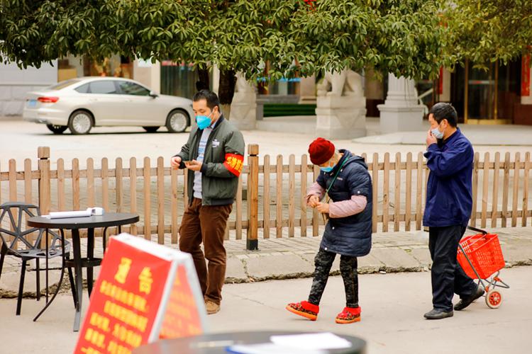 2月19日,五嶺農耕文明博物館的黃臻,他在查看居民的出入證。有一天他寫了一篇我們在這里辛勤值守的報道,結果第二天就被抽到紀委去上班了。
